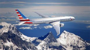 American Airlines airplane flying over mountains covered in snow